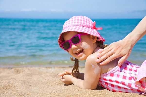 Mom anoints protective cream back a little girl on the beach