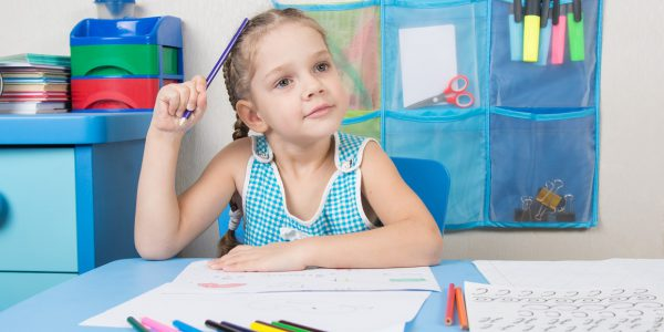 Five-year girl scratched his head and wondered pencil drawing picture at table