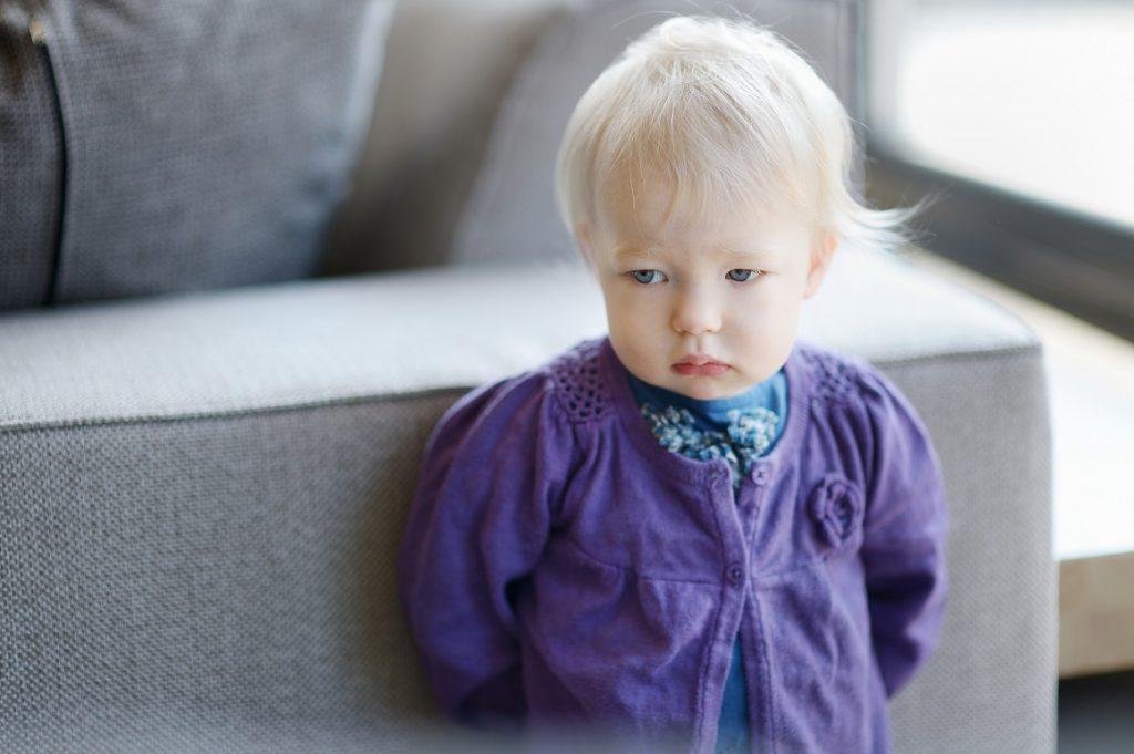 Sad toddler girl portrait indoors