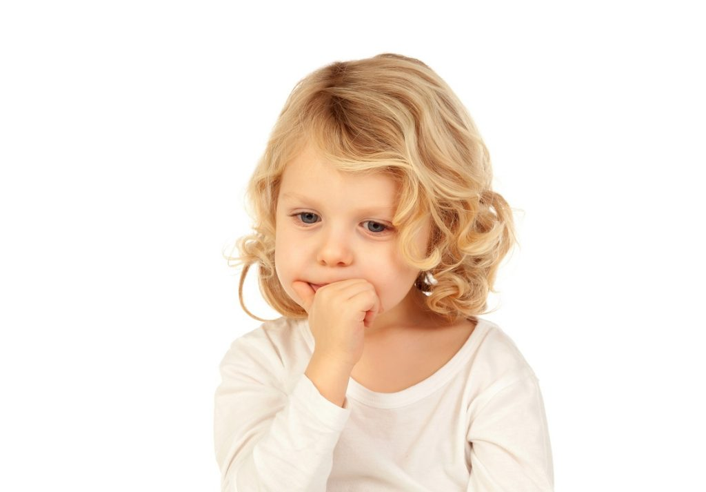 Small blond child bitting his nails isolated ona  white background