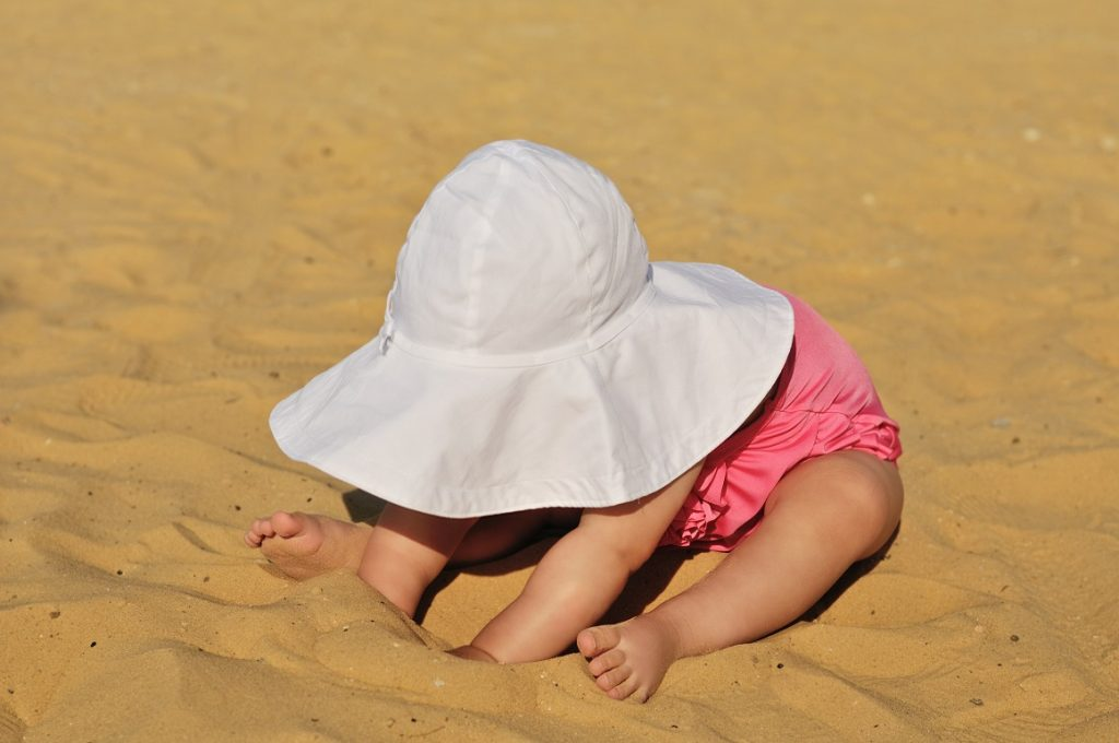 fashion baby on the beach  playing with sand