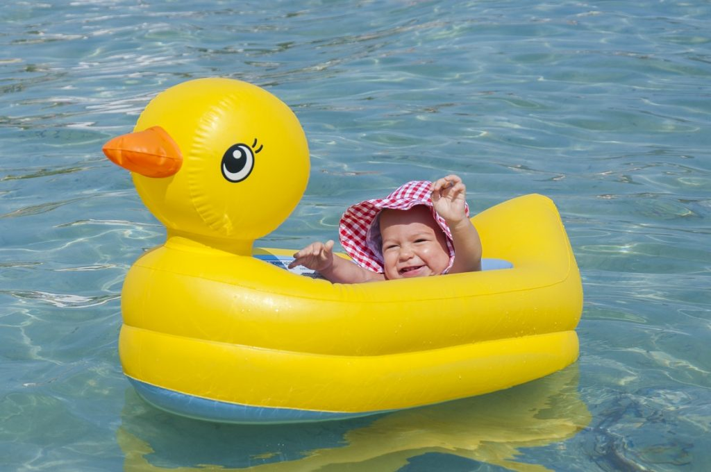 Little baby float in the yellow duck boat. Selective focus on the baby
